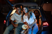 Diverse Young Couple Having Romantic Date. Cheerful Guy And His Girlfriend Watching A Movie, Sitting Together In Car Trunk In Front Of A Screen In An Open Air Cinema