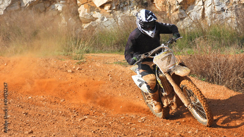 Zoom photo of professional motocross rider on his motorcycle on extreme dirt and mud terrain track Fototapet