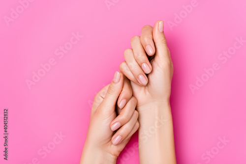 top view of female hands with pastel nail varnish on fingernails on pink background