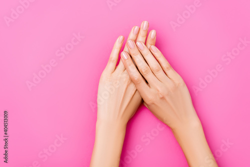 Obraz top view of groomed female hands with glossy fingernails on pink background - fototapety do salonu