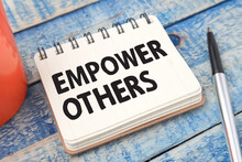 Empower Others, Text Words Typography Written On Paper Against Wooden Background, Life And Business Motivational Inspirational