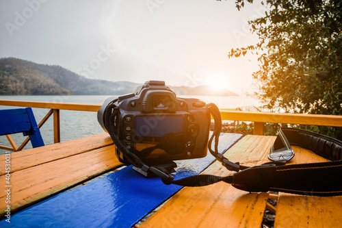 Close-up Of Camera On Wooden Table Against Sea During Sunset