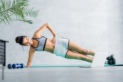 Fototapeta premium happy african american sportswoman exercising in side plank pose on fitness mat near laptop and dumbbells
