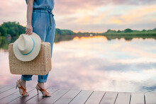 Young Traveling Woman Holding Vintage Suitcase, Hat And Standing On Pier With Relaxing Mood And Watching Beautiful View Of Woods And Blue Sky And Clouds On Vacation. Selective Focus, Copy Space