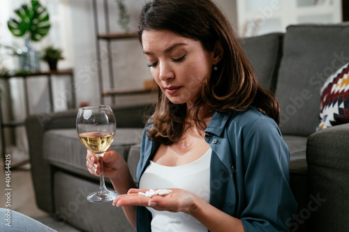 Depressed woman is drinking wine and taking pills at home alone. Alcohol and drug addiction concept.