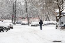 Snowfall And Frost In Urban Environments. Man, Cars And Buildings Are Covered In Snow