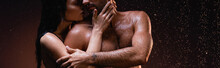 Cropped View Of Sensual Woman Hugging And Kissing Sexy Muscular Man Under Rain On Dark Background, Banner