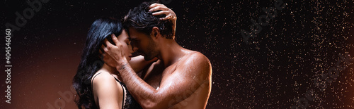 Fototapeta side view of couple embracing and kissing under rain on dark background, banner obraz