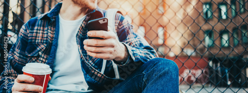 man sitting on the city street resting with cup of hot coffee and using mobile phone. Wide screen, panoramic