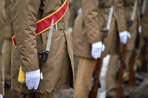 Fotografiet Military guard of honor holding rifles in rest position participate at a funeral