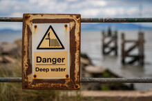 Sign: Danger, Deep Water - With Blurry Background, Seen In Silloth, Cumbria, England, UK