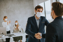 Young Business Men Handshaking In The Office With Protective Facial Masks