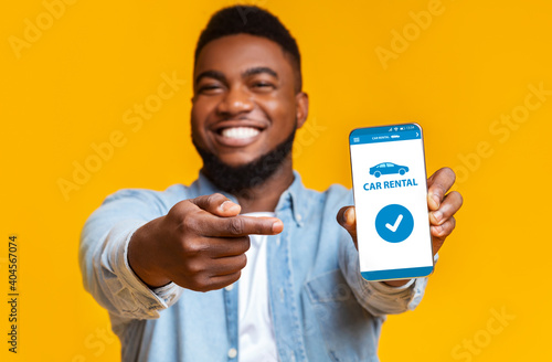 Cheerful Black Guy Pointing At Smartphone With Car Rental App On Screen
