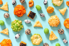 Pattern From Various Japanese Snacks On A Blue Background. Top View, Flat Lay. Rice Crackers With Wasabi And Nori, Peanuts With Sesame Seeds, And Other Snacks. Mix Traditional Japanese Snack Food.