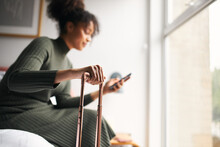 Woman With Suitcase Checking Out Of Boutique Hotel Sitting On Bed Waiting For Taxi Ordered On Mobile Phone App