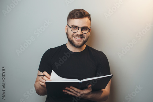 Fotografie, Obraz Bearded man is wearing glasses while holding a book and smile at camera on a gra