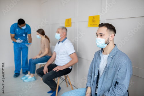 Obraz Young Caucasian man waiting in line for covid-19 vaccine injection at clinic. Medical care and health services - fototapety do salonu