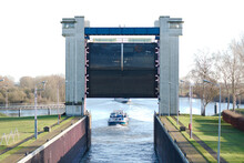 A Ship In A Sluice Gate On A River. Sluice Gate Is Open. Shipping Channel And Sluice Construction.