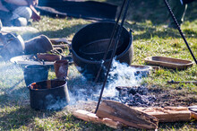 Homemade Food In Iron Pot, A Cauldron In Smoke Near Dying Embers, Historical Reenactment Of Slavic Or Viking Lifestyle.