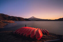 Mount Fuji At Sunset By The Lake Kawaguchi With A Clear Sky And Sunset Tones And A Set Of Red Boats By The Shore On The Foreground