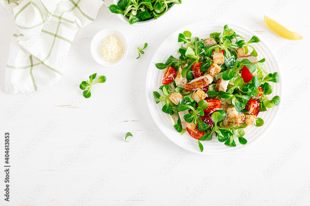 Fototapeta Caesar salad with grilled chicken meat, fresh tomato, croutons, lambs lettuce and parmesan cheese. Healthy lunch. Top view