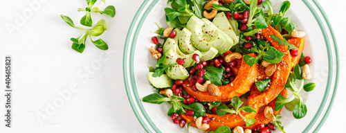 Fototapeta Fresh vegetable salad with lambs lettuce, baked butternut squash or pumpkin, avocado, pomegranate, cashew and almond nuts. Healthy vegetarian food concept. Top view. Banner obraz