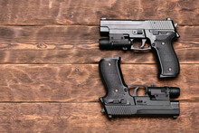 Two Toy Guns With Laser Sights On The Brown Wooden Table Background With Copy Space.