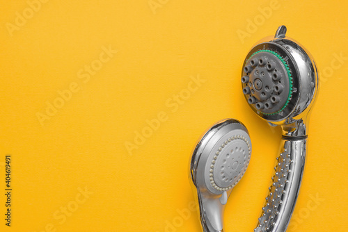 Obraz Two different old shower heads on the yellow flat lay background with copy space. Replacement of shower head concept. - fototapety do salonu