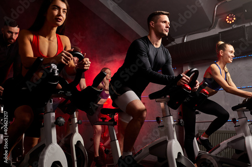 Fototapeta premium people exercising, legs cardio training on bicycle in fitness gym, for good healthy. bodybuilder, lifestyle, exercise fitness, workout and sport training concept