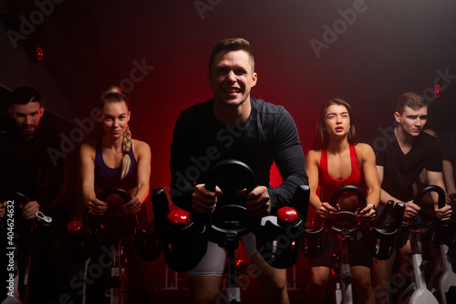Fototapeta premium sportsman diligently riding an exercise bike in gym, the guy is exercising on a stationary bike