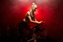 Fit Woman Riding On The Spinning Bike At Gym, Exercising Alone, In Smoky Room With Red Neon Lights