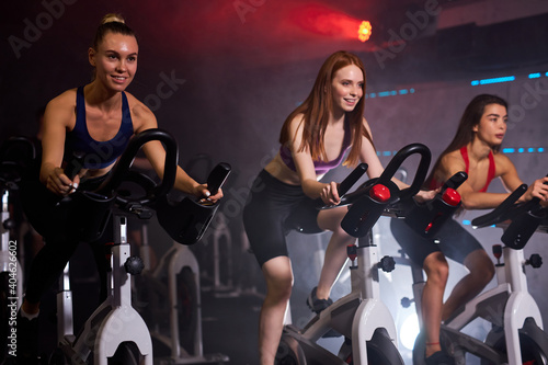 Obraz na plátně group of sporty people in gym, perfect shaped muscular people training on bicycl