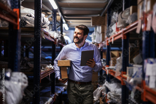 Obraz Smiling bearded businessman walking trough storage of shipping firm, holding boxes under armpit and using tablet to check on goods. - fototapety do salonu