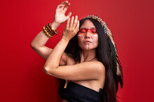 Tribal Indian Woman Dancing During Ritual, Female Has Ethnic Make-up On Face, Wearing Shaman Costume Isolated Over Red Background