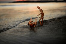 Wooden Man Is Saving Falling Wooden Guy At Beach At Sunset. Close Up Shoot