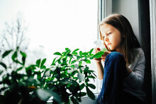 Little Girl Watering Flowers At Home On The Window, Splashing On Plant Leaves