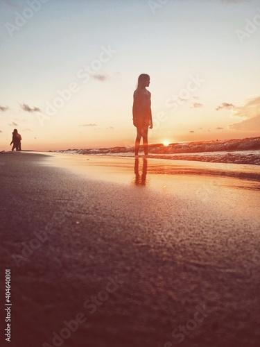 Obraz Girl Standing At Beach Against Sky During Sunset - fototapety do salonu