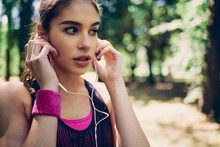 Portrait Of Female Runner Standing In Nature And Putting Earphones In Ears.