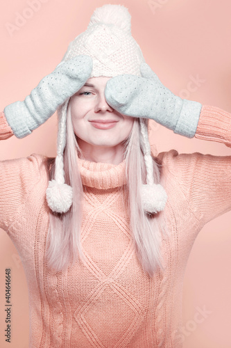 elegant young girl in a winter hat, warm sweater and mittens