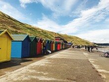 Multi Colored Beach Huts At Beach Against Cloudy Sky