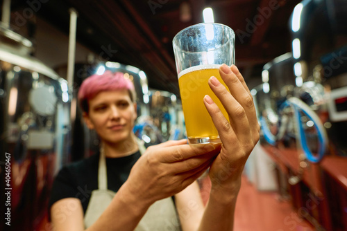 Obraz Hand of female brewer in apron examining glass of fresh beer after preparation - fototapety do salonu
