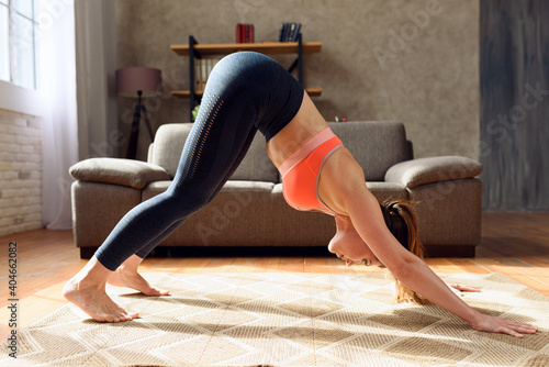 Obraz Young woman does gym exercises. She is at home due to coronavirus codiv-19 quarantine - fototapety do salonu