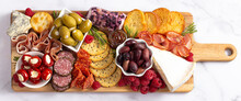 A Savoury Charcuterie Board Covered In Meats Olives Peppers Berries And Cheese