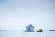 Grain Silo On Winter Field With Farm Tractors