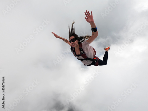 Stampa su Tela Young woman parachutist in the clouds free fall