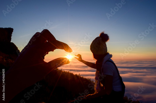 Obraz Close-up Of Person Gesturing While Woman Looking At Sun Against Sky During Sunset - fototapety do salonu