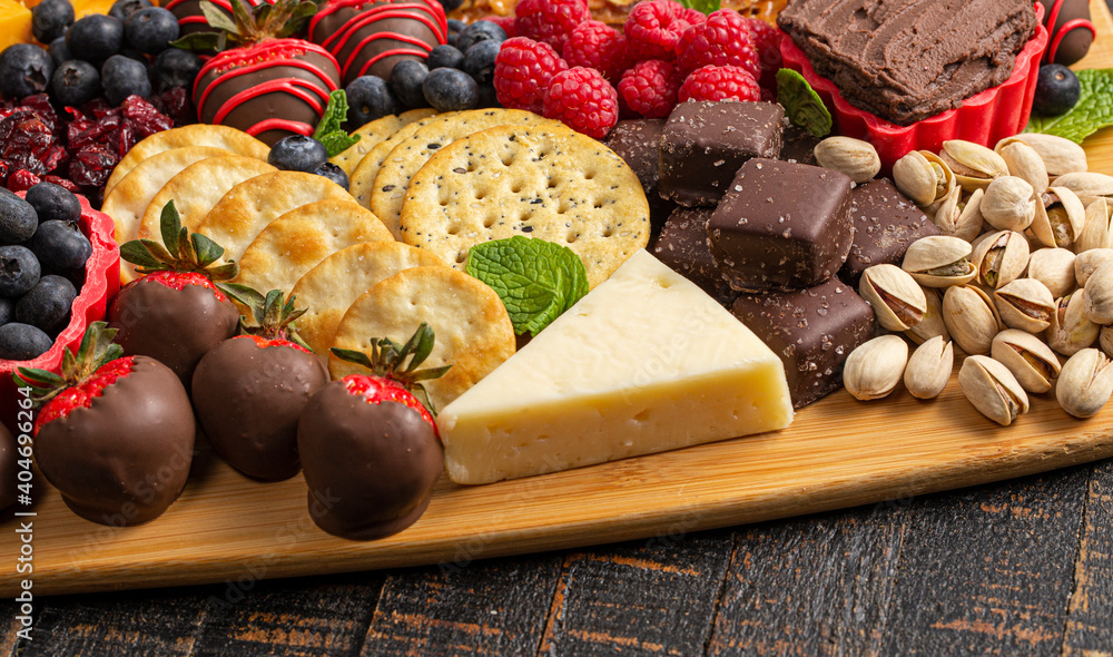 Fototapeta A Chocolate Covered Strawberries and Cheese Sweet Charcuterie Board on a Rustic Wooden Table