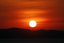 Full Orb Of The Sun Setting With The Sky Glowing Orange Over A Silhouetted Island And Ocean, Southeast Asia.