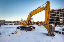Yellow Excavator On The Background Of A New Monolithic House Under Construction In Winter