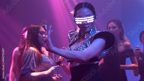 Obraz Group of people dance in disco night club to the beat of music from DJ on stage . New year night party and nightlife concept . - fototapety do salonu